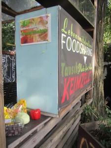 """Rückseite des FairTeilers im Gemeinschaftsgarten """"Keimzelle"""" mit Food-Sharing-Banner"""