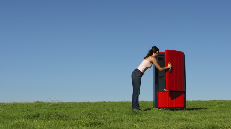 Ein roter Kühlschrank steht im Freien, eine Frau sieht hinein: Tauschkühlschränke sind eine Möglichkeit zum Lebensmittelretten, zum Beispiel von Foodsharing e.V., dem Verein von Filmemacher Valentin Thurn.