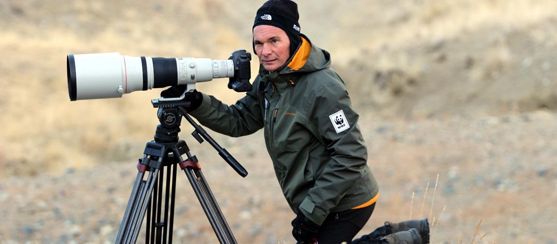 Naturfotograf Thorsten Milse kniet in der mongolischen Wildnis vor seiner Kamera auf einem Stativ. Das Bild wird vom riesigen Objektiv der Kamera dominiert.