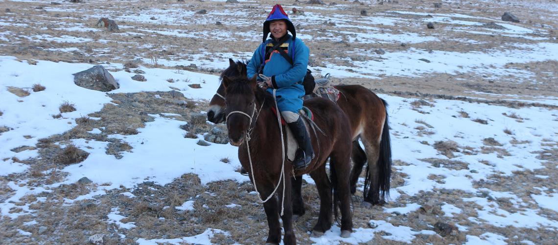 Mongole in traditioneller Kleidung auf Pferd in verschneitem Gebirge: Kollege Muknast aus der Mongolei bricht auf zum Fallencheck.