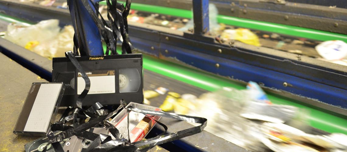 Musikkassetten und Videobänder mit ordentlich Bandsalat in einer Müll-Sortiermaschine.