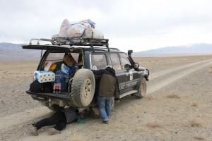 Jeep in der Steppe, Mann liegt darunter: Reifenpanne.