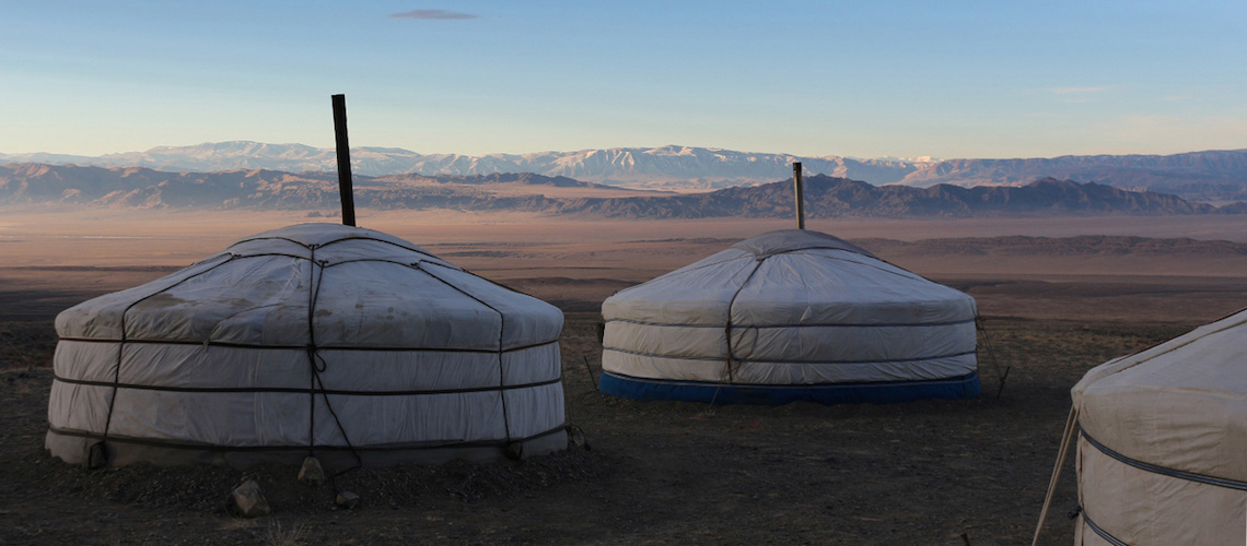 Drei runde, weiße Zelte in großer Weite: Expedition in die Mongolei - unser Ger-Camp.