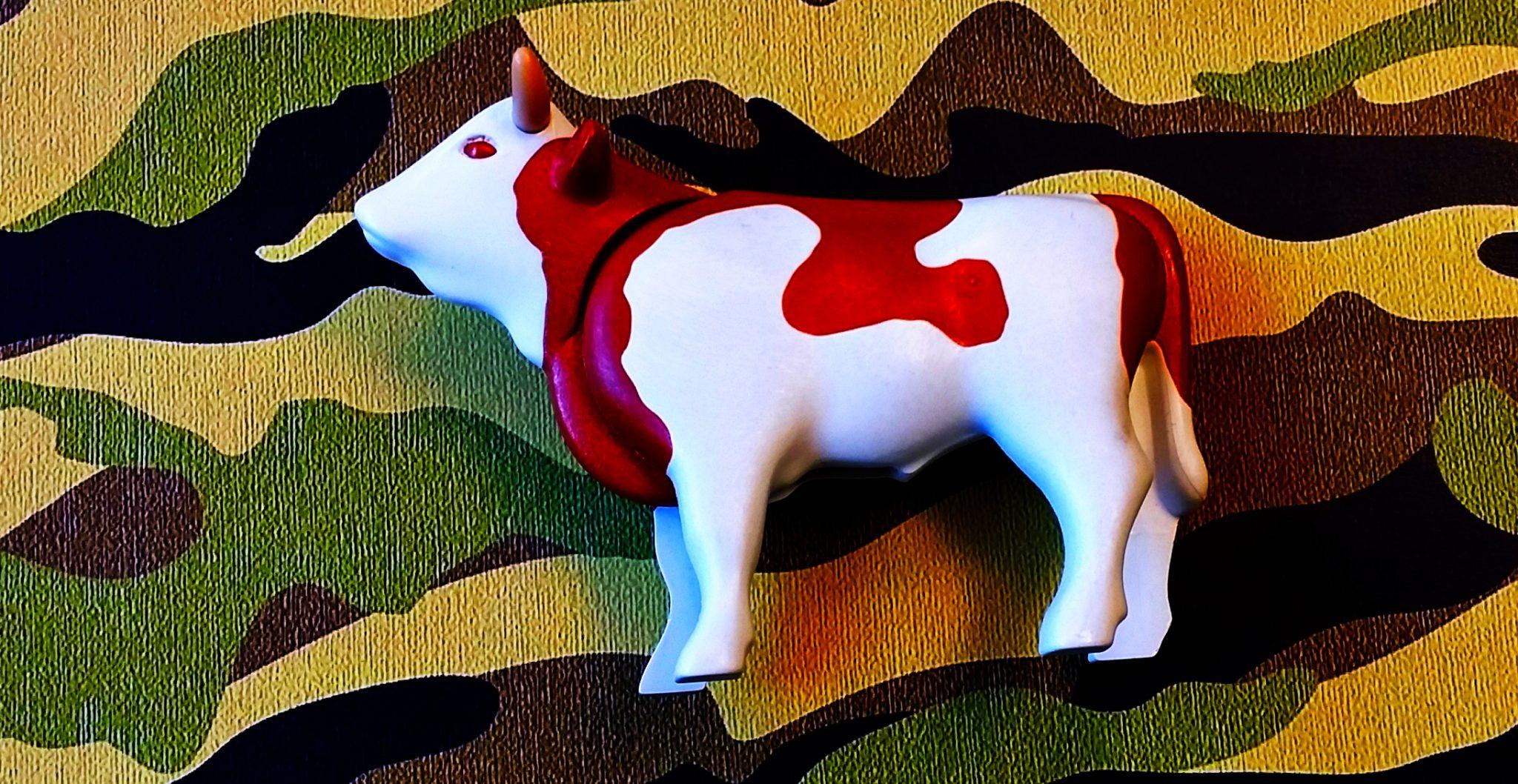 Plastikkuh vor einem Camouflage-Hintergrund.