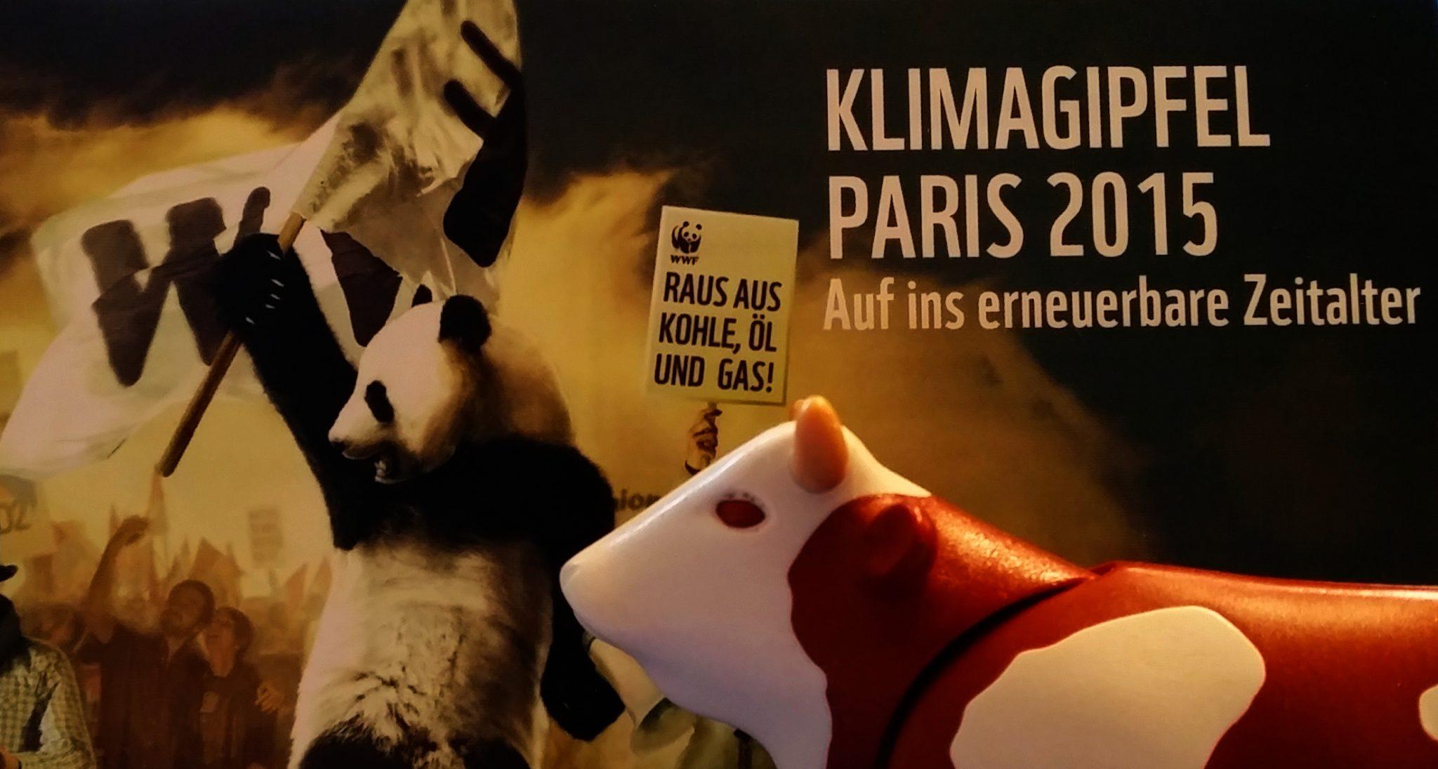 Plastikkuh vor WWF-Plakat zum Klimaschutz.