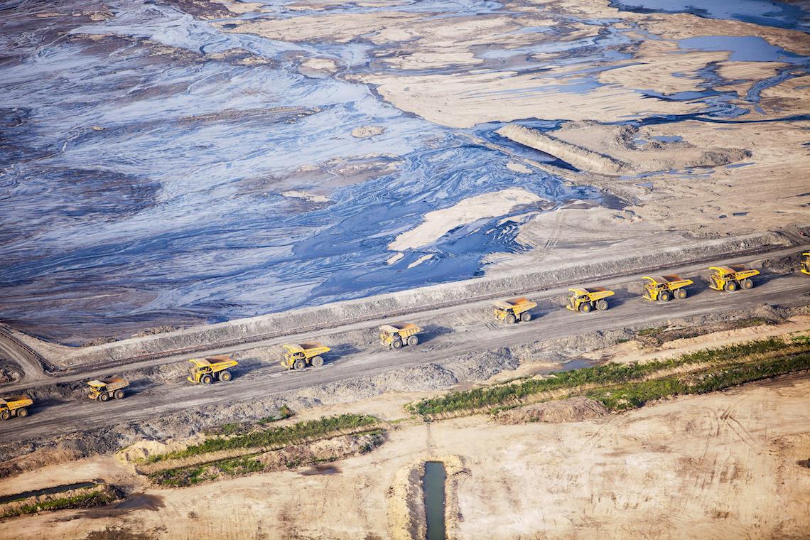 Riesige Laster in zerwüsteter Umgebung: Ölsand-Mine im Norden von Fort McMurray, Alberta, Kanada.