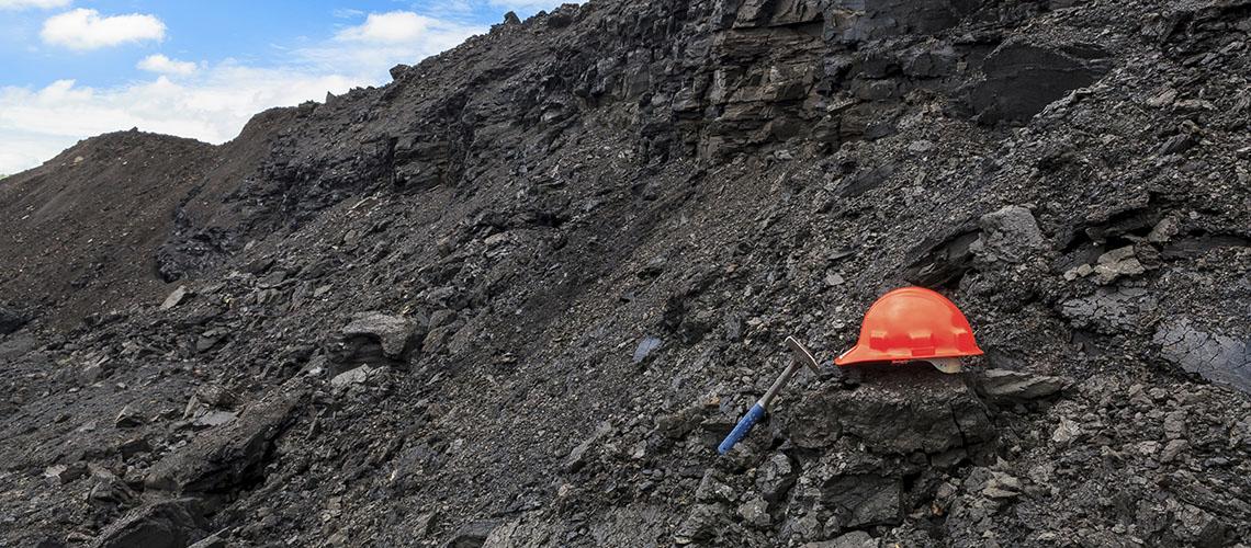 Schmutzige Kohle: Ein Helm liegt auf einer Kohlehalde: Lautb der Studie Dark Cloud sterben jährlich tausende Menschen an den Emissionen aus der Kohleverstromung verfrüht