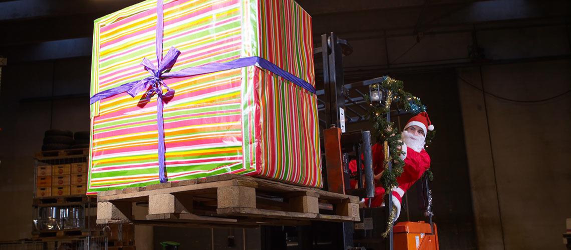 weihnacht: Weihnachtsmann mit Geschenkstapel und Gabelstapler