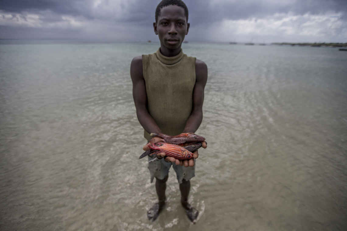 isherman holding fish in his hands, Mafamede, Mozambique. Mafamede is part of the protect area of Primeiras e Segundas.