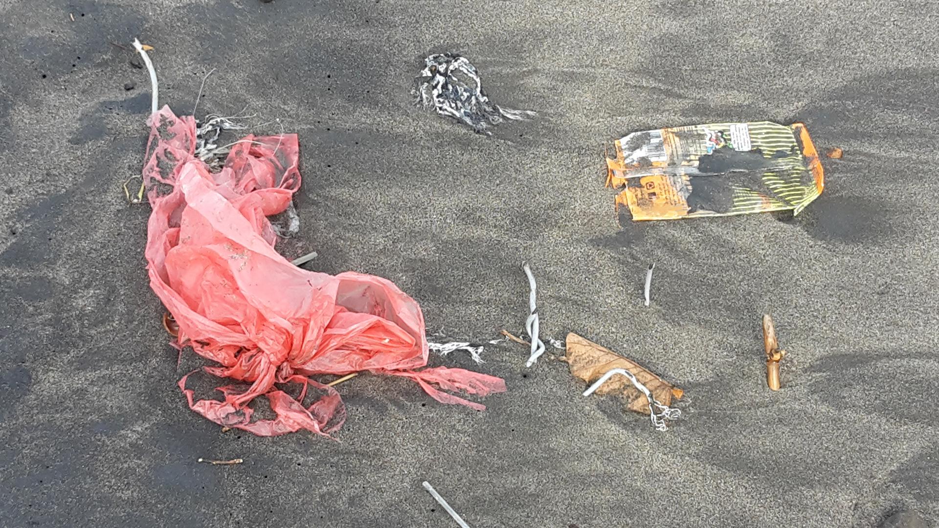 Strand in Canggu auf Bali: Eine Plastiktüte und weiterer Plastikmüll aus dem Meer, angespült zur Regenzeit.