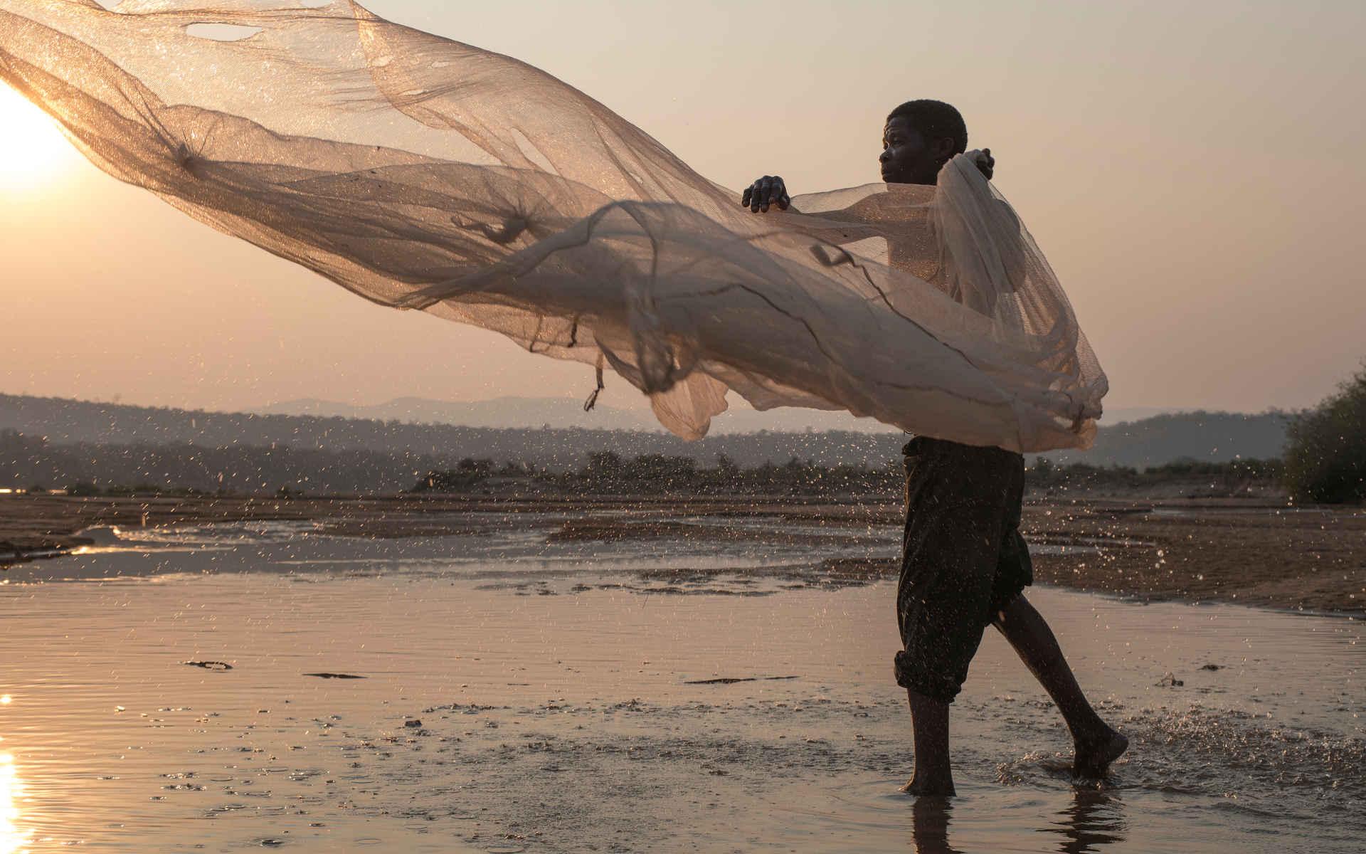 Fischfang: Fischer in sambia wirft sein netz aus