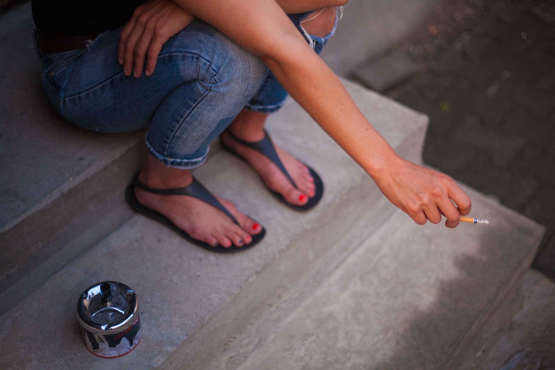 Rauchen und Umwelt: Frau raucht mit Aschenbecher