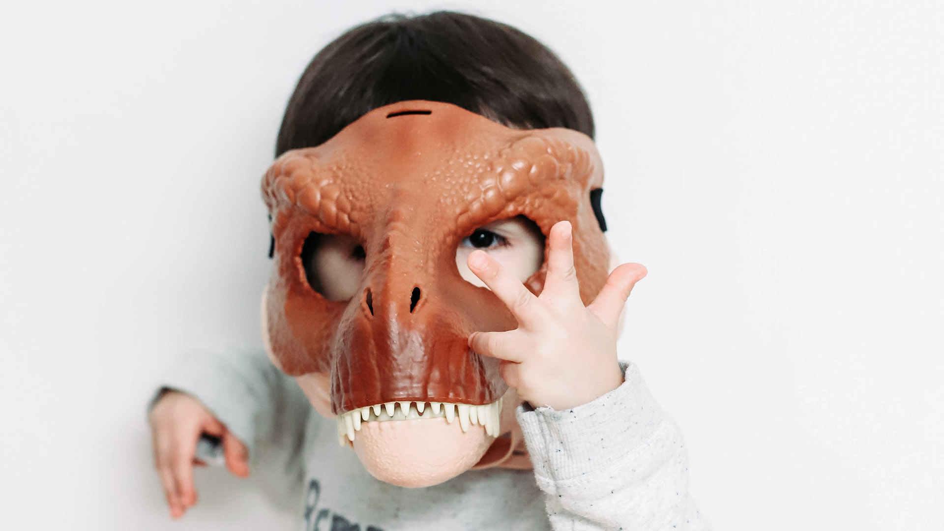 Schaffen wir Massenausterben aufzuhalten? Kind mit Dinosauriermaske