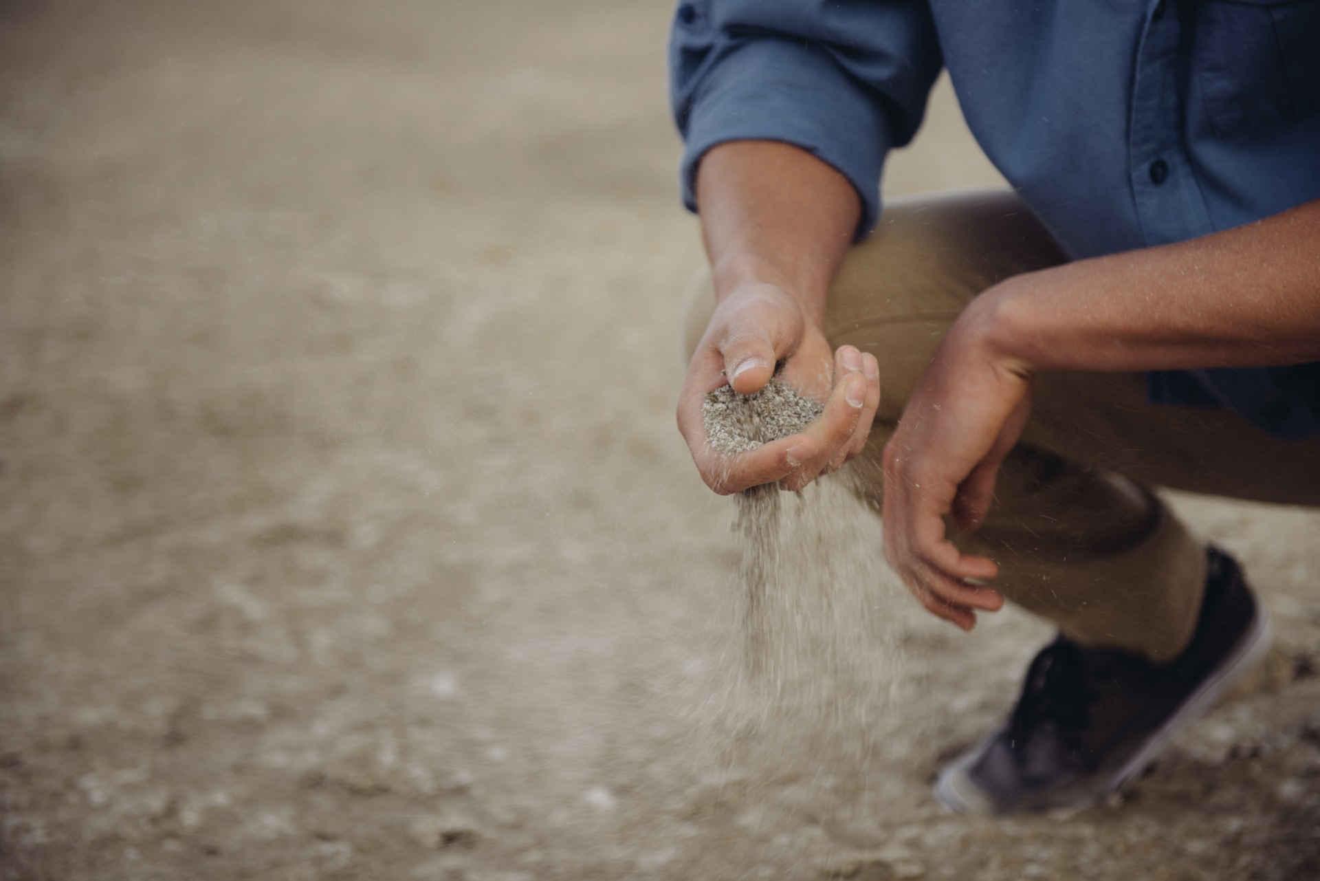Wasser: Mann lässt Sand durch die Finger rinnen