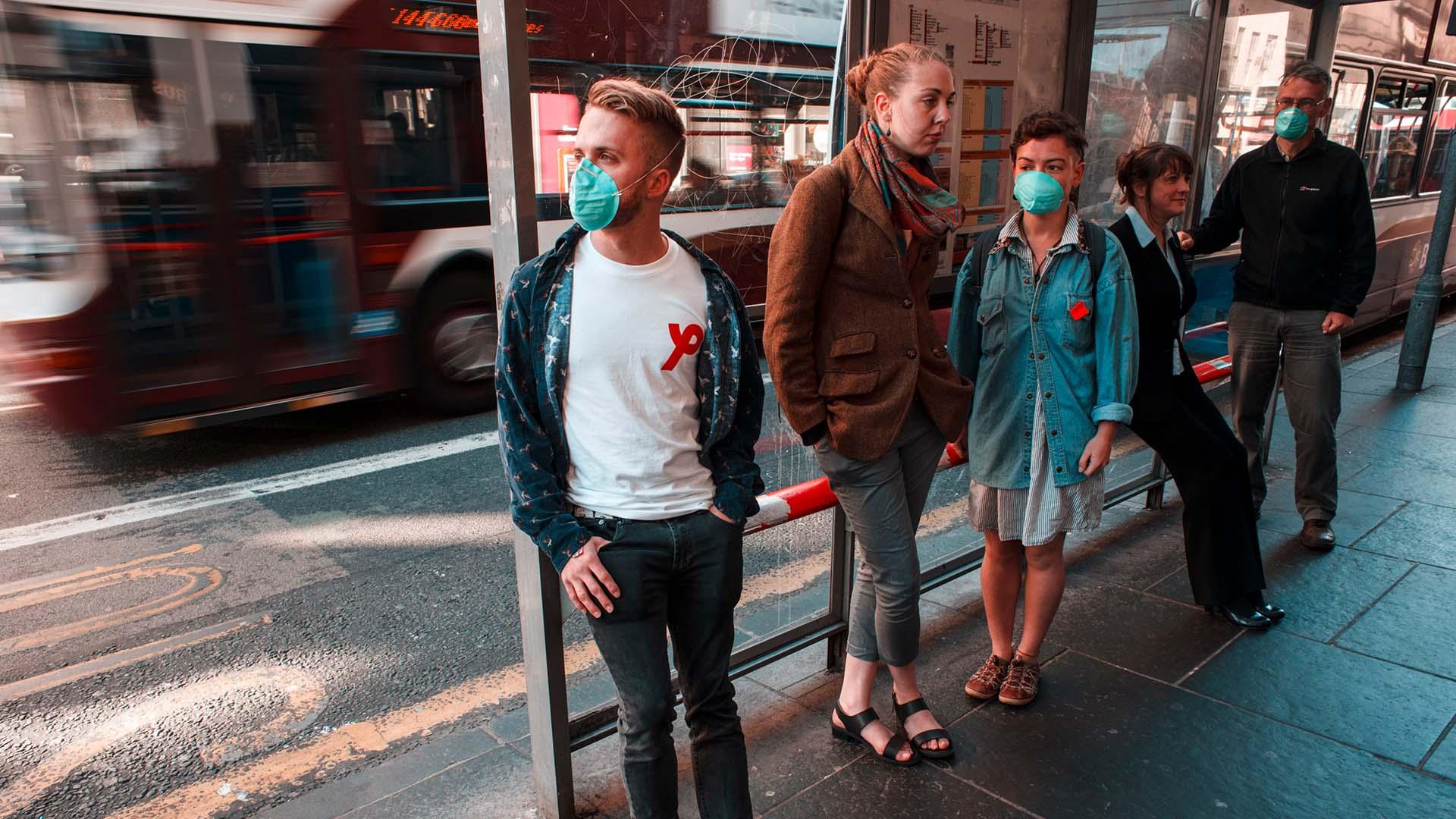 Klima und Gesundheit: Menschen mit Schutzmasken an einer Bushaltestelle
