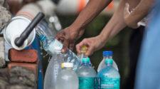Menschen füllen Wasserflaschen auf