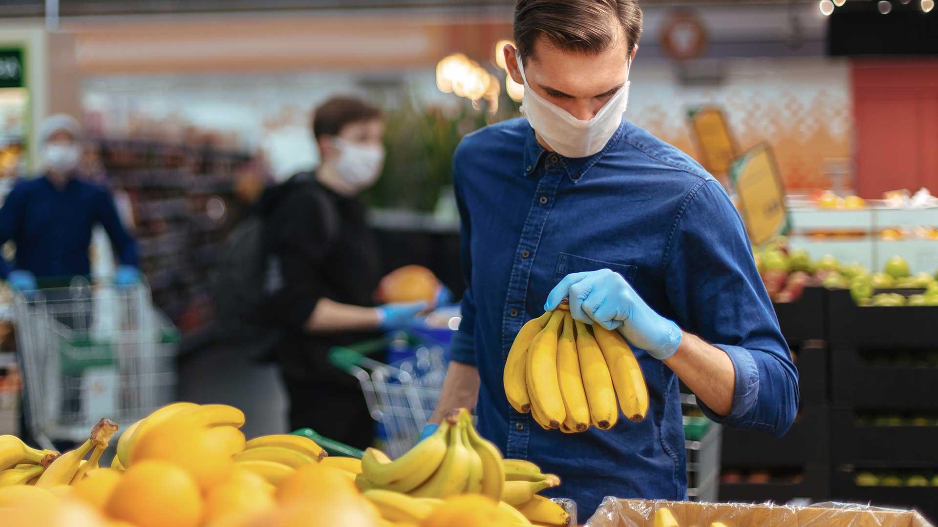 Bananen im Supermarkt: Mann mit Maske kauft ein