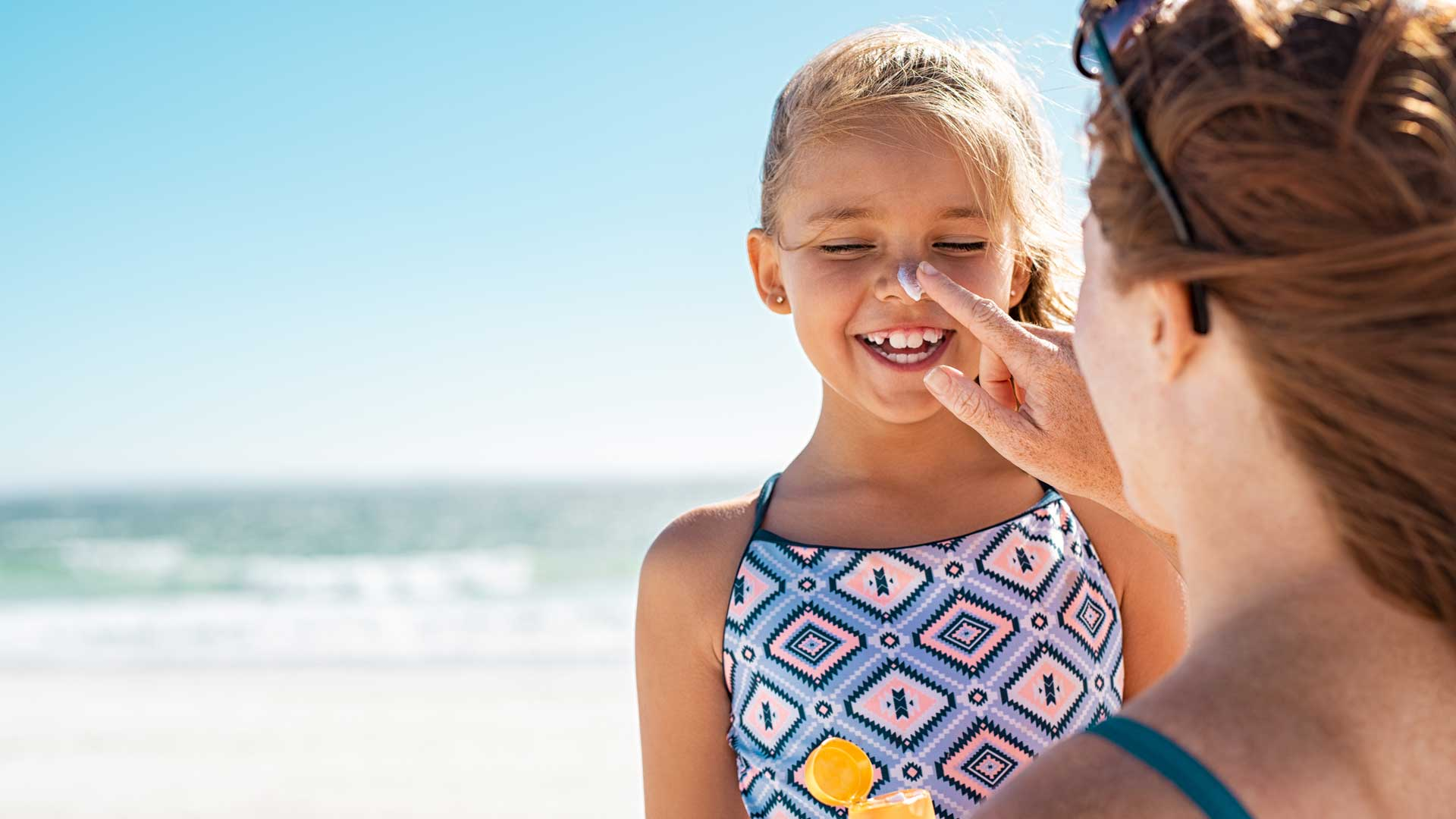 Sonnencreme am Strand mit Kind