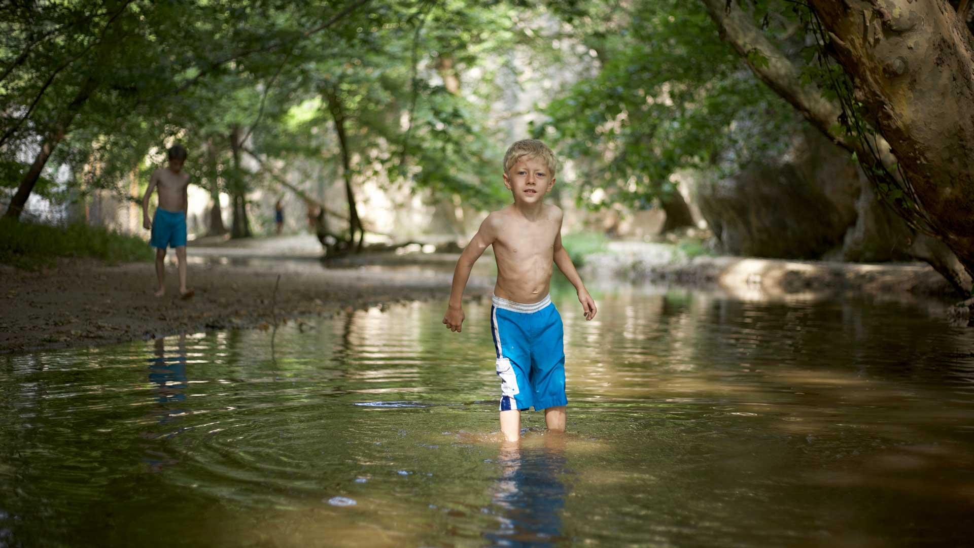 Sonnencreme: Junge an einem schattigen Waldsee