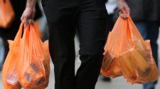 Ein Mann trägt mehrere orange Plastiktüten