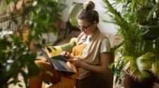 Frau arbeitet zuhause zwischen Pflanzen