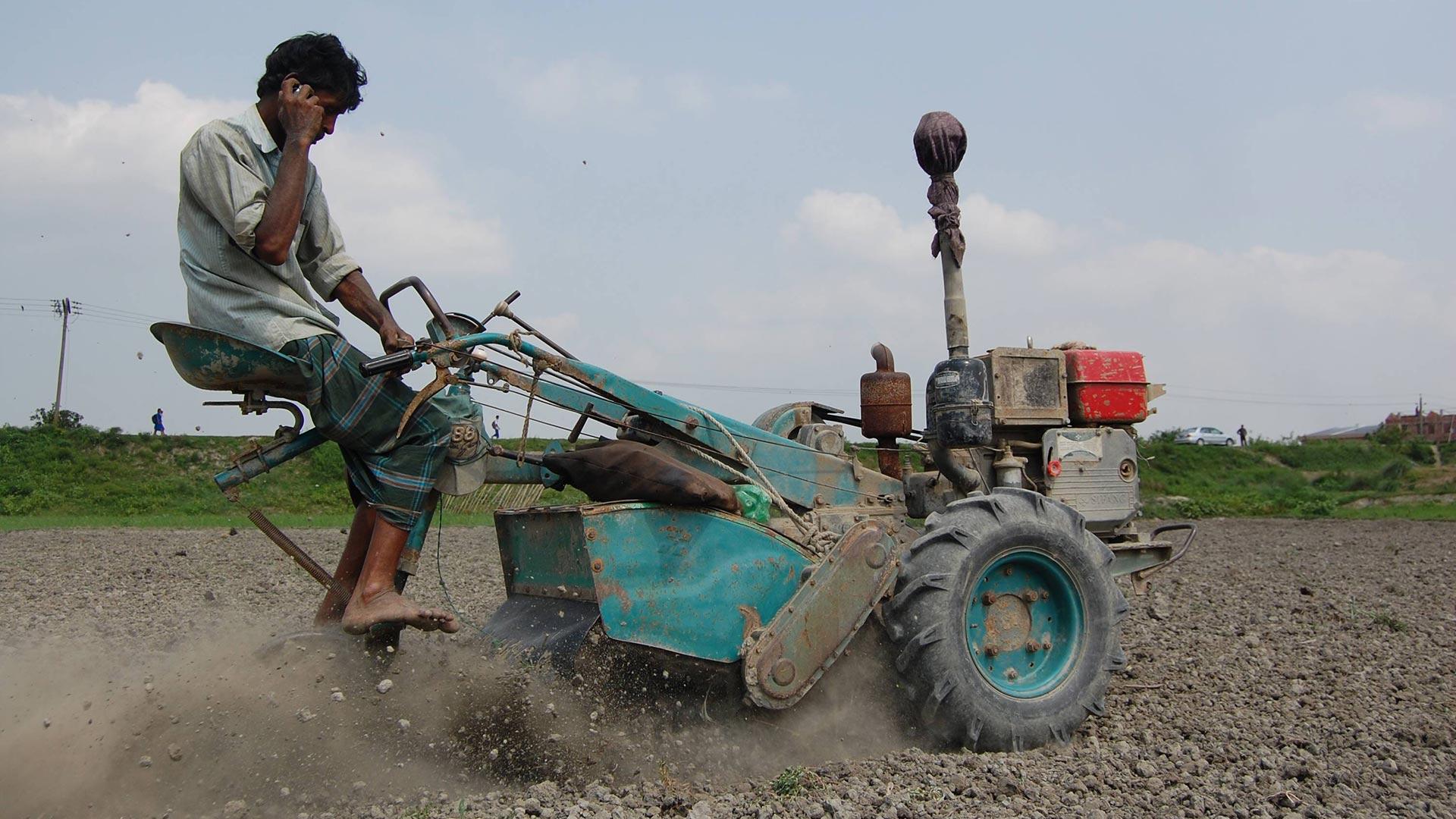 Kleinbauer auf einer Maschine mit Handy