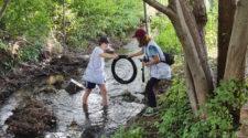 clean Up Walk: WWF Jugend holt einen alten Reifen aus einem Bach